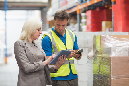 Manager using tablet while worker scanning package in warehouse photo