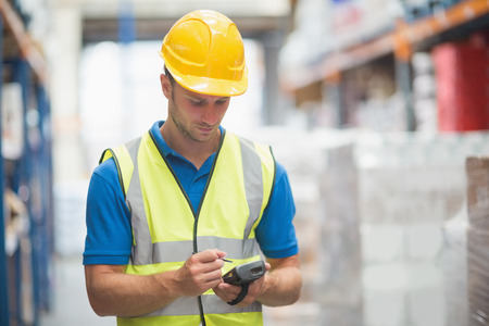 hand held: Worker utilizzando computer palmare in magazzino
