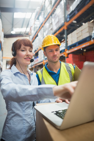 happy workers: Smiling businesswoman wearing headset using laptop in warehouse