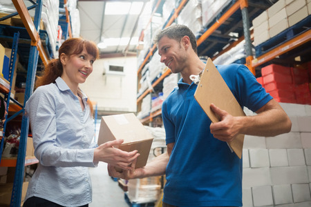 Delivery man passing parcel to warehouse manager in warehouse