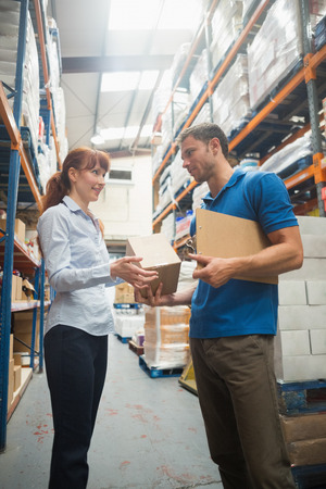 loading bay: Delivery man passing parcel to warehouse manager in warehouse Stock Photo