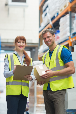 loading bay: Smiling warehouse manager and delivery man in warehouse