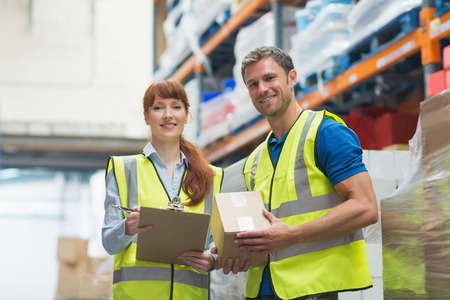 warehouse: Smiling warehouse manager and delivery man in warehouse
