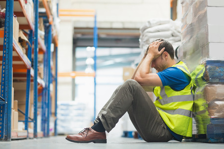 exhausted: Tired man sitting on the couch with a headache in warehouse