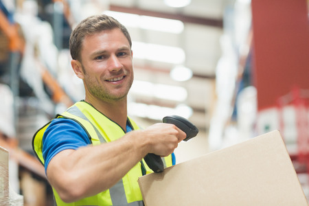 warehouse worker: Smiling manual worker scanning package in warehouse