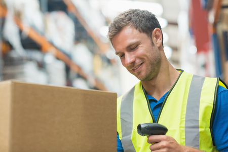 warehouse: Smiling manual worker scanning package in warehouse