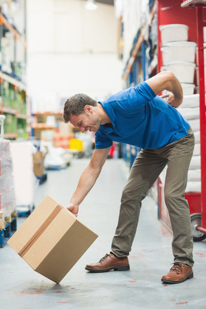 wincing: Side view of worker with backache while lifting box in the warehouse