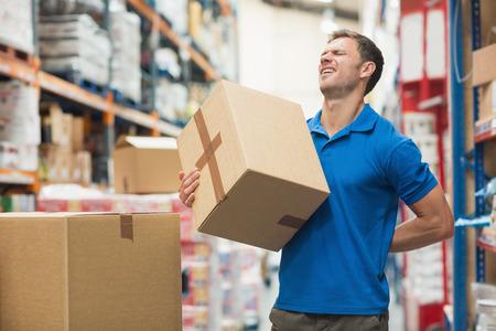 detras de: Vista lateral del trabajador con el dolor de espalda, mientras que la caja de elevación en el almacén