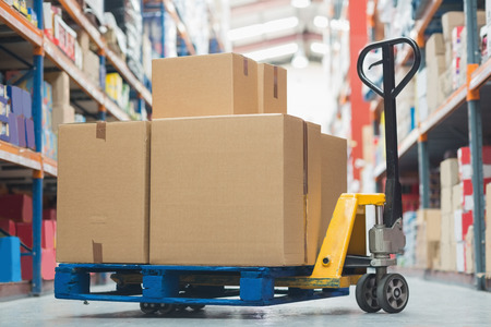 cardboard boxes: Cardboard boxes on trolley in warehouse Stock Photo