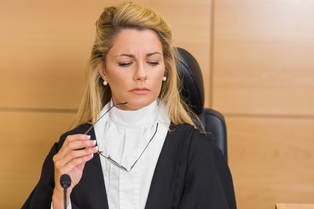 trial indoor: Stern judge looking and listening in the court room Stock Photo