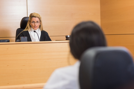 female lawyer: Lawyer listening to the judge in the court room