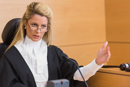 female judge: Stern judge speaking to the court in the court room Stock Photo