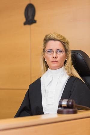 trial indoor: Stern judge looking at camera in the court room Stock Photo