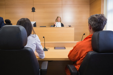 sentencing: Lawyer and client listening to judge in the court room Stock Photo