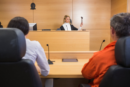 orden judicial: Abogado y cliente escuchando a juzgar en la sala del tribunal