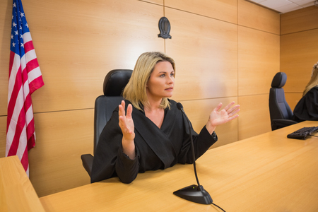 stern: Stern judge speaking to the court in the court room Stock Photo