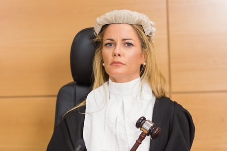 female judge: Stern judge sitting and listening in the court room