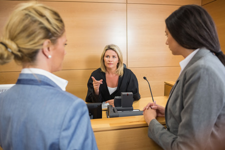 female lawyer: Lawyers speaking with the judge in the court room
