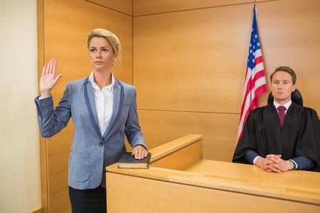 orden judicial: Testigo prestando juramento en la sala del tribunal