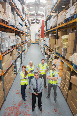 Team standing behind their boss in warehouse