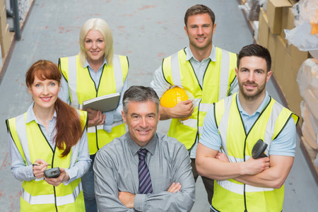 work      wear: Team standing behind their boss in warehouse