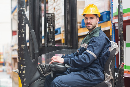 forklift truck: Portrait of driver operating forklift machine in warehouse
