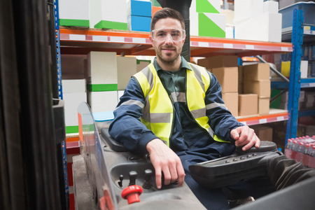 forklift: Smiling driver operating forklift machine in warehouse