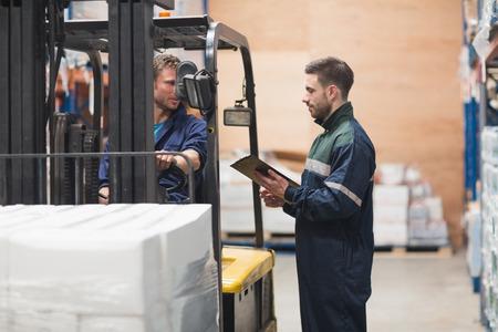 carretillas almacen: Trabajador del almac�n hablando con conductor de montacargas en casa de las mercanc�as