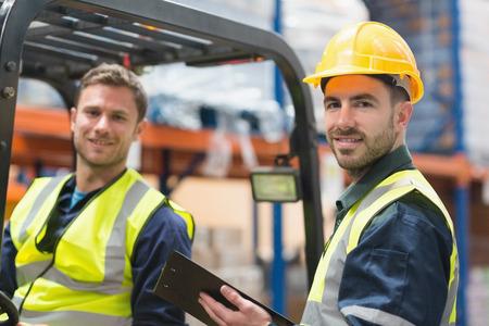 Glimlachen magazijnmedewerker en heftruckchauffeur in magazijn Stockfoto