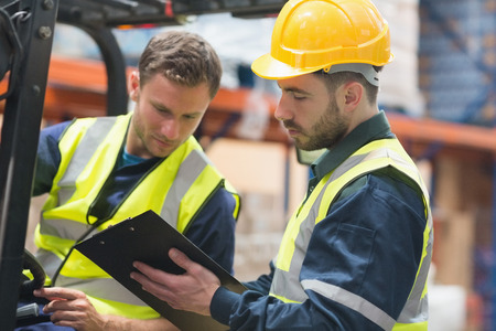 focused: Focused warehouse workers talking together in warehouse Stock Photo
