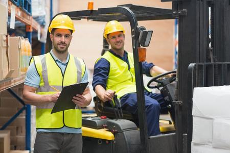 carretillas almacen: Sonriente trabajador de almac�n y conductor del montacargas en almac�n Foto de archivo