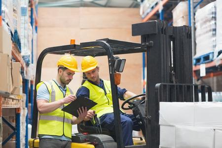 carretillas almacen: Trabajador del almac�n con conductor hablando carretilla elevadora en almac�n Foto de archivo