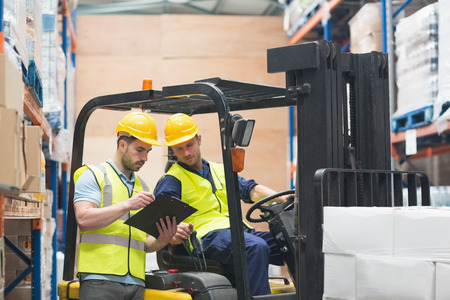 forklift driver: Warehouse worker talking with forklift driver in warehouse Stock Photo