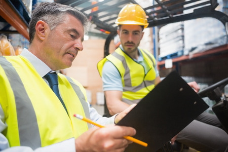 forklift driver: Forklift driver talking with his manager in a large warehouse