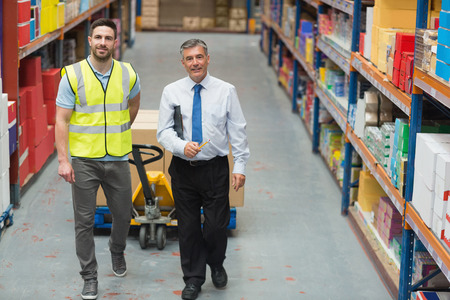 young adult men: Warehouse worker talking with his manager in a large warehouse