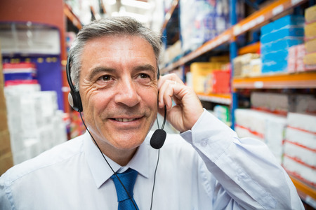 manage transportation: Warehouse manager giving orders on headset in a large warehouse