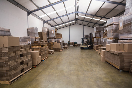 forklift: Forklift amid rows of boxes in a large warehouse Editorial