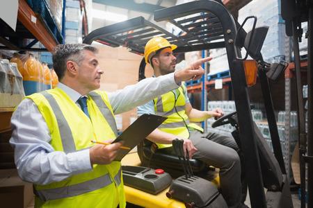 Heftruckchauffeur praten met zijn manager in een groot magazijn