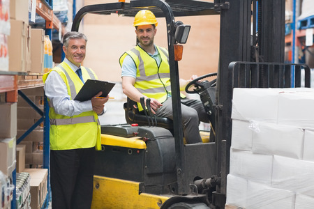 Driver operating forklift machine next to his manager in warehouse photo