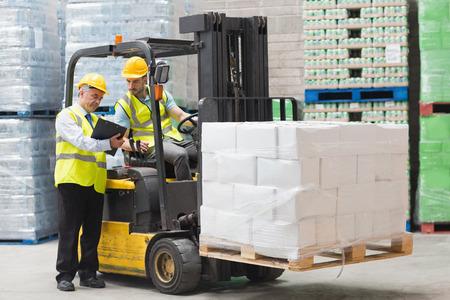 Řidič vysokozdvižného vozíku mluví s jeho manažerem ve velkém skladu