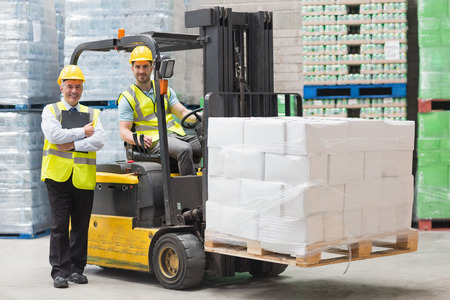 Driver bedienen heftruck machine naast zijn manager in magazijn Stockfoto