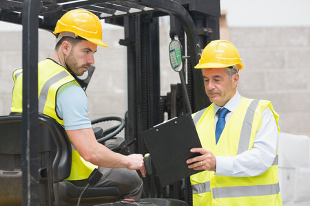 Forklift driver talking with his manager in a large warehouse photo