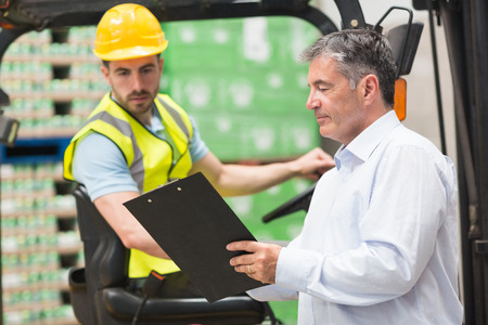 forklift: Forklift driver talking with his manager in a large warehouse