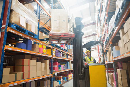 forklift driver: Focused driver operating forklift machine in warehouse Stock Photo