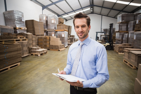 Portrait of smiling manager holding clipboard in warehouse photo