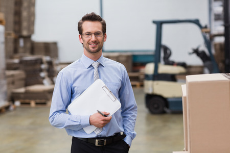 Portrait of manager holding clipboard in warehouse Foto de archivo