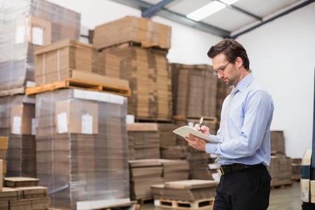 gerente: El gerente de almac�n de comprobar su inventario en un gran almac�n Foto de archivo