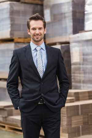 Smiling manager in suit standing with hands in pockets in a large warehouse photo