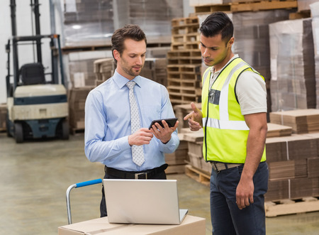 warehouse: Warehouse worker talking with his manager in a large warehouse