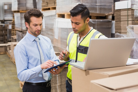 distribution warehouse: Warehouse worker and manager working together in a large warehouse Stock Photo